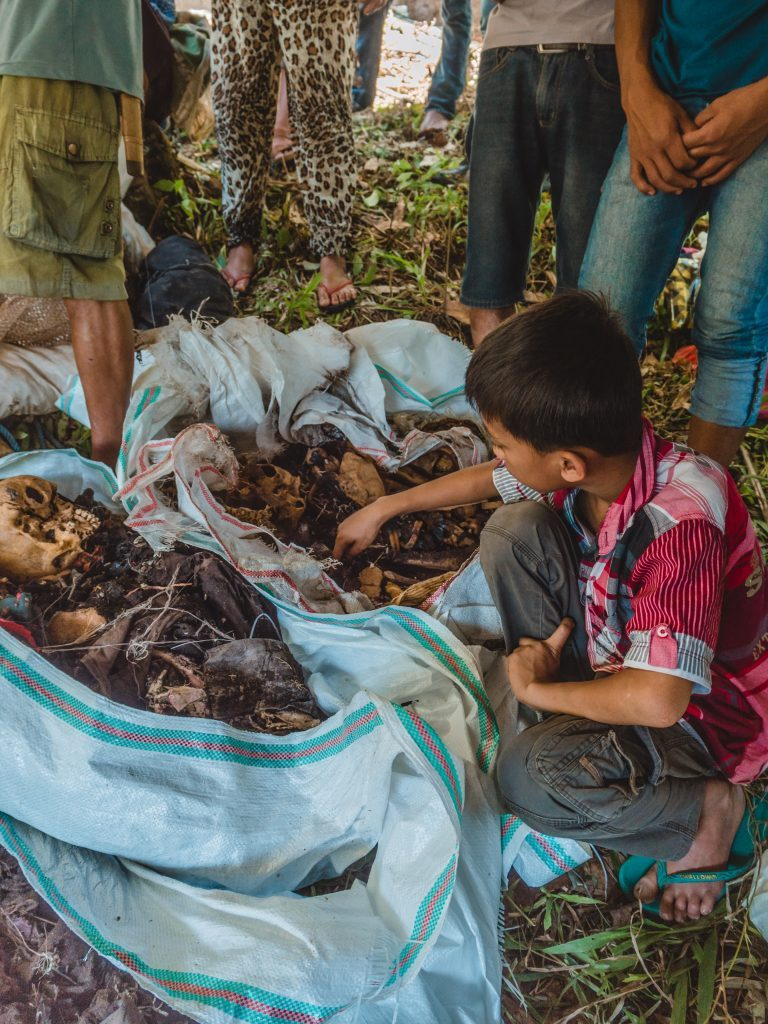 A boy plays with the bones of a skeleton in Tana Toraja at the manene ceremony