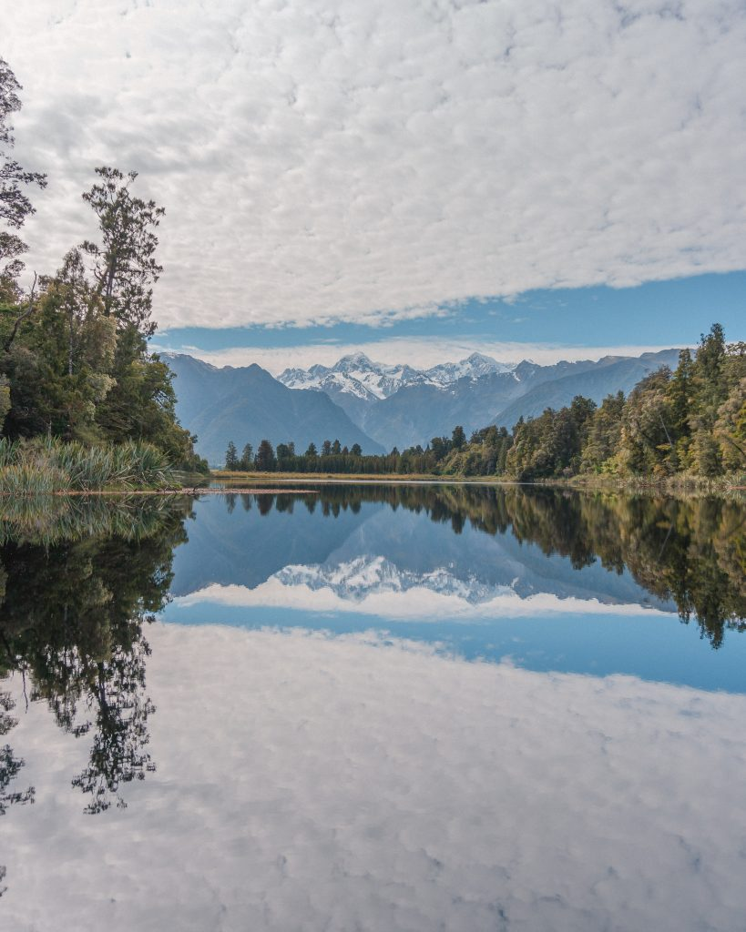 The beautiful mirror lake of Lake Matheson is a must see in New Zealand with great views of Mount Cook in the distance