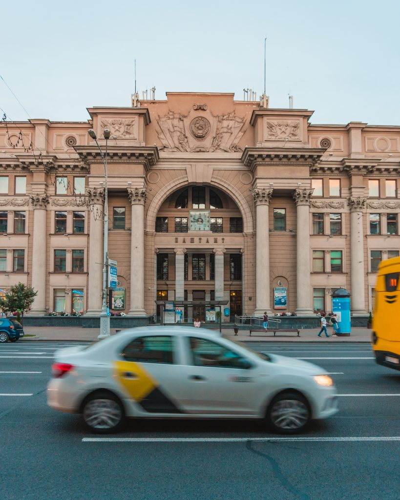 A taxi in Minsk drives past the Central Post Office. The best taxi app in Minsk is Yandex Taxi.
