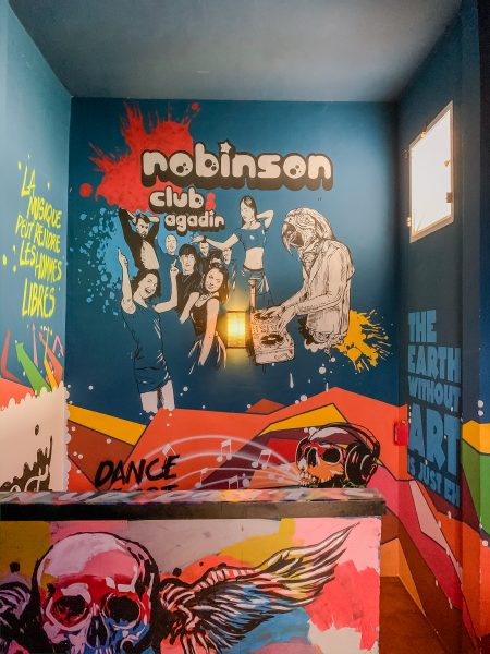 """Yes, the ROBINSON Club in Morocco even has a night club! They have some very cool wall art on the walls as you walk down the stairs to the club, showing different images of people dancing, a DJ doing his set, a skull with rainbow wings and even a quote that says """"the EARTH without ART is just EH""""."""